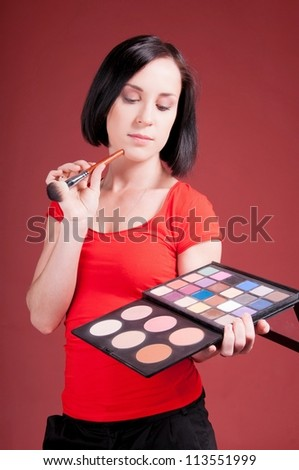 Beautiful young woman holding different make-up shadow and rouge