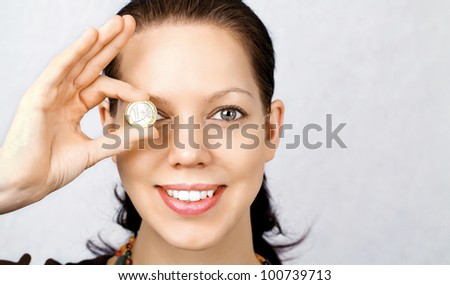 Beautiful young woman holding 1Euro coin in front of her eye