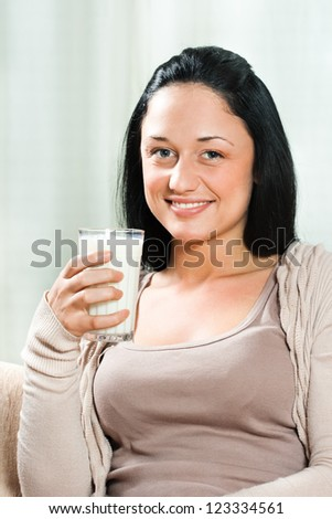 Beautiful young woman holding glass of milk,Healthy refreshment