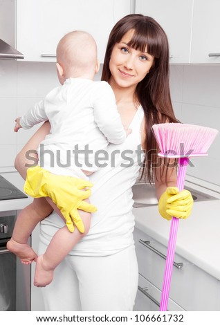 beautiful  young woman holding her baby and cleaning the furniture in the kitchen