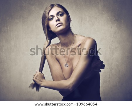 Beautiful young woman holding her hair in her hands and wearing a necklace
