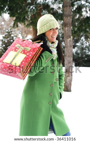 beautiful young woman holding holiday shopping bag in outdoor winter setting