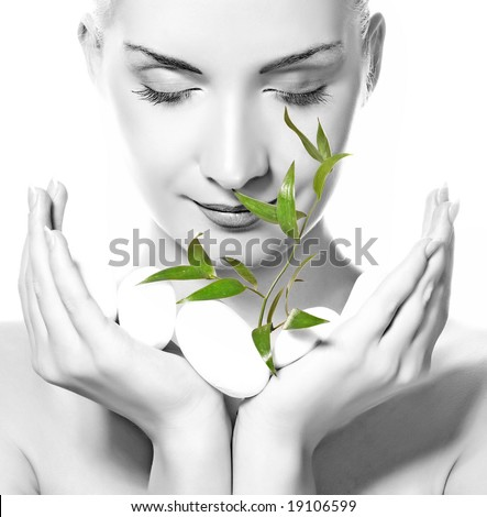 Beautiful young woman holding plant growing up through stones