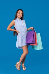 Beautiful young woman holding shopping bags and looking at the camera while standing against blue background.