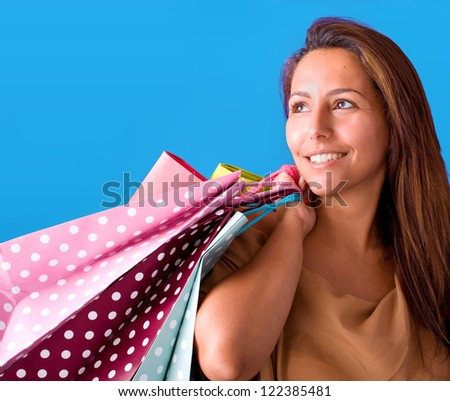 Beautiful young woman holding shopping bags, isolated on blue studio background.