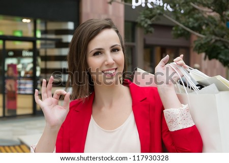 Beautiful young woman holding shopping bags, showing the sign OK and smiling to camera in front of store. Girl show approved sign by hand