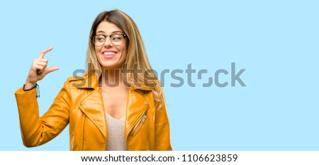 Beautiful young woman holding something very tiny, size concept
