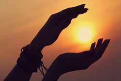 Beautiful young woman holding sun in hands on sunset, silhouette