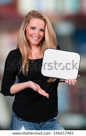 Beautiful young woman holding up a blank sign