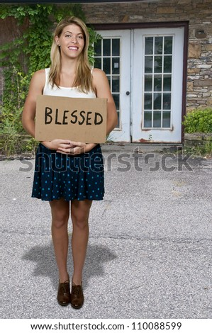 Beautiful young woman holding up a sign that says Blessed