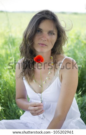 Beautiful young woman holds a poppy, sitting in a romantic meadow