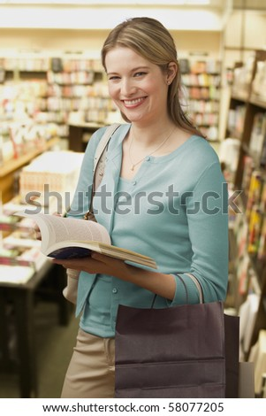 Beautiful young woman holds an open book in a bookstore while smiling towards the camera. Vertical shot.