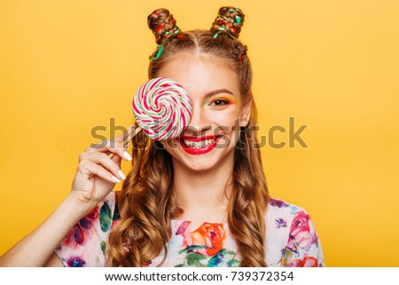Beautiful young woman holds in hand candy #739372354