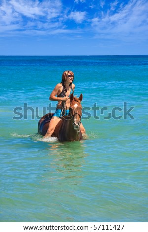 Beautiful young woman horse riding in tropical ocean