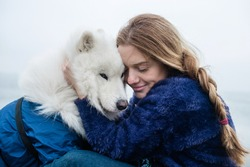 Beautiful young woman hugs her fluffy Samoyed dog, outdoors. Close-up portrait of a contented girl with long hair hugging a purebred dog. Smiling woman enjoying a nice day.