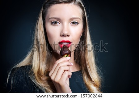 Beautiful young woman in a black dress holding delicious strawberry covered with black chocolate, isolated on a black background