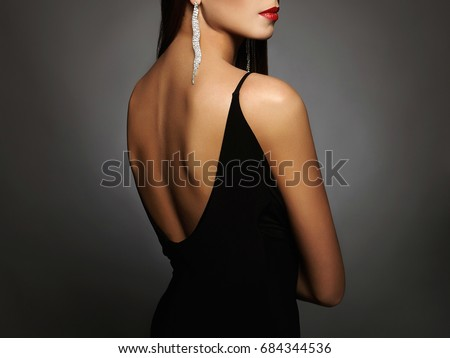 beautiful young woman in a black sexy dress with open back wearing jewelry.girls back
