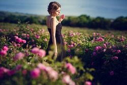 Beautiful young woman in a blooming rose garden. The concept of perfume advertising.