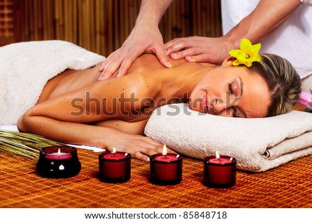 Beautiful young woman in a day spa getting massage. Relax.