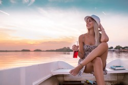 Beautiful young woman in a dress sitting on the boat and enjoying in a beautiful sunset while drinking beer.