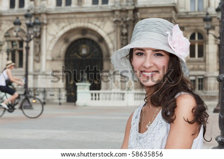 Beautiful young woman in a fashion pose in a historic plaza in Paris, France.