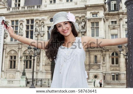 Beautiful young woman in a fashion pose in a Parisian plaza.