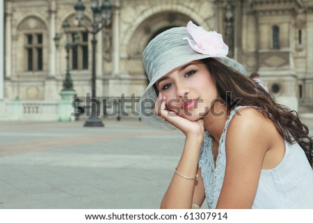 Beautiful young woman in a fashion pose in a typical french plaza in Paris, France.
