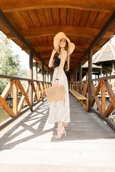 Beautiful young woman in a fashionable wicker straw hat in a summer stylish skirt with a lace chemise with a stylish handbag resting on sunny holidays