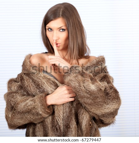 beautiful young woman in a fur coat with finger on mouths keeping silence