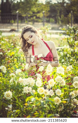 Beautiful young woman  in a garden of roses at sunny summer day
