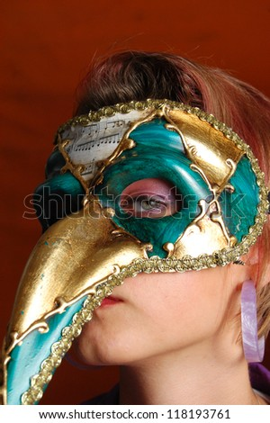 Beautiful young woman in a green and gold mysterious venetian mask