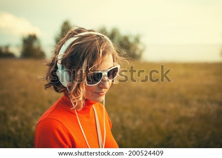 Beautiful young woman in a headphones listening music in the park Instagram