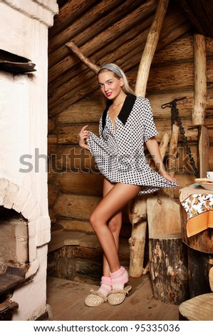 Beautiful young woman in a log farmhouse.