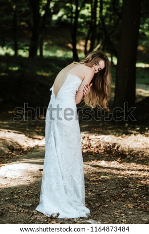 Stock Photo Beautiful young woman in a long dress in the mountains.