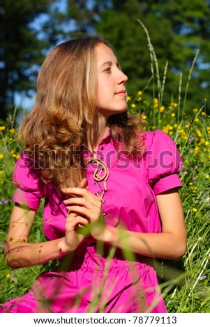 Beautiful young woman in a meadow full of flowers