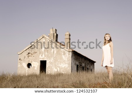 Beautiful young woman in a meadow with a old abandoned house