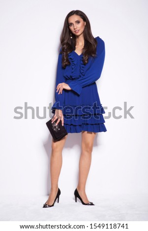 Beautiful young woman in a nice fashionable blue dress. Christmas new year glamour photo.