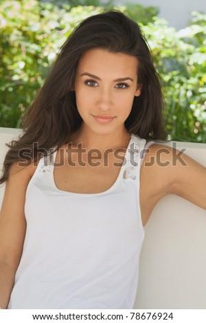 Beautiful young woman in a outdoor garden patio setting.