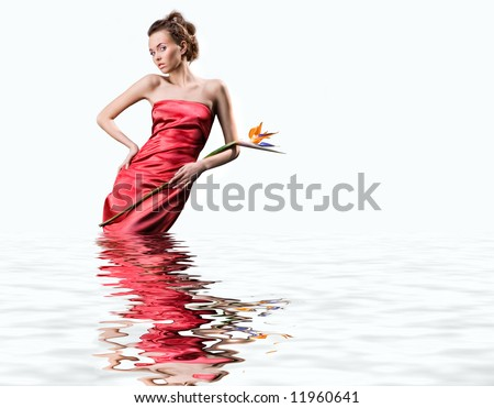 Beautiful young woman in a  red dress stands in the water. Holds an exotic flower in a hand