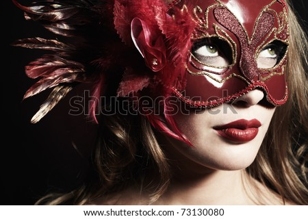 Beautiful young woman in a red mysterious venetian mask - stock photo