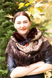 Beautiful young woman in a Russian colored scarf on the background of autumn nature.