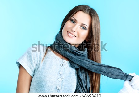 Beautiful young woman in a scarf, over blue background.