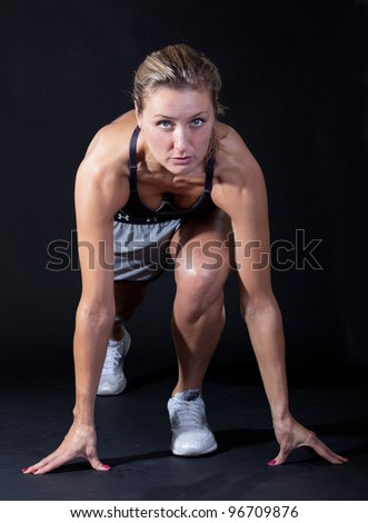 Beautiful young woman in a sprinters crouch