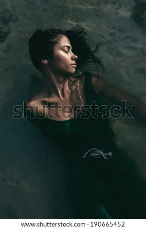 Beautiful young woman in a summer dress lying on her back in shallow water at the beach with her head turned to the side and her long black hair floating free