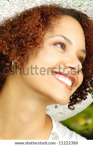 Beautiful young woman in a summer hat laughing outdoors