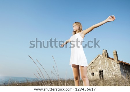 Beautiful young woman in a white dress relaxing in a meadow close to the sea