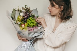 Beautiful young woman in a white shirt holding a bouquet of mixed unusual original flowers in gray paper on a white background. Chrysanthemum green, yellow orchid flower, pink rose and green leaves.