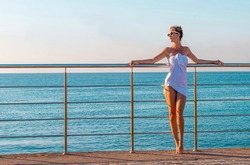 beautiful young woman in a white tunic posing on the sea promenade against the background of the blue sea in the rays of the setting sun