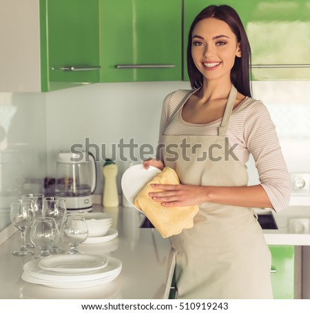 Beautiful young woman in apron is wiping the dishes, looking at camera and smiling while cleaning in kitchen
