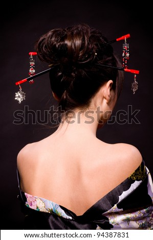 Beautiful young woman in Asian costume on black background.
